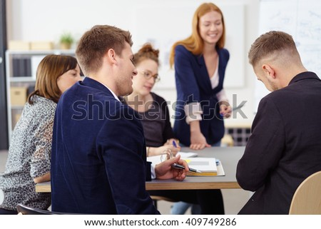 Group of five young adult male and females in small office meeting at conference table with happy expressions - stock photo