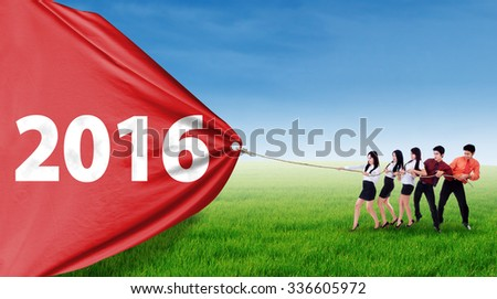Group of five young entrepreneur pulling a big banner with numbers 2016 on the meadow - stock photo