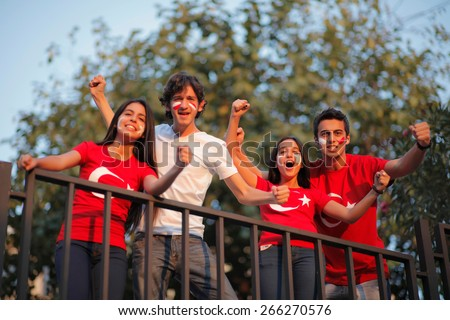Group of football fans cheering with their faces painted - stock photo