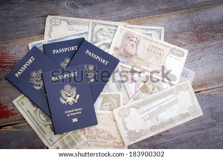 Group of four American passports with foreign banknotes in different currencies lying on a wooden table depicting planning and financing for a vacation and travel - stock photo