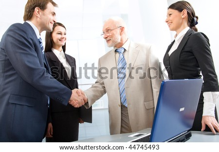 Group of four business people shaking hands in an office - stock photo