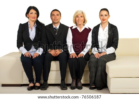 Group of four business people sitting on a beige couch in a line isolated on white background - stock photo