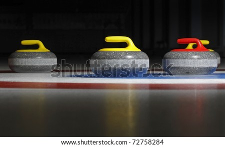 Group of four curling stones in the rings with dark background and ice reflection. - stock photo