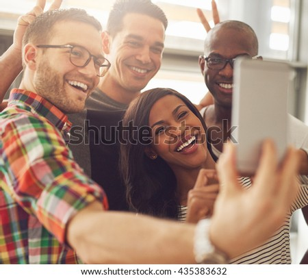 Group of four diverse cheerful co-workers taking self portrait and making funny gestures with hands at small office in front of bright windows