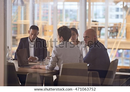 Group of four dynamic business executives sitting together in a meeting about their company's future in the firms newly renovated conference room.