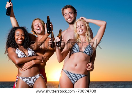 Group of four friends - men and women - standing with drinks on the beach against the setting sun over the ocean - stock photo