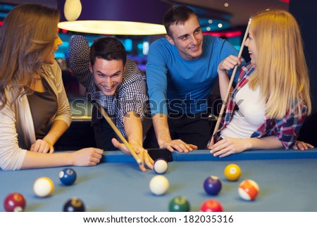 Group of four friends playing billiard - stock photo