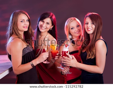 Group of four happy beautiful young female friends celebrating in a nightclub with glasses of cocktail in their hands - stock photo