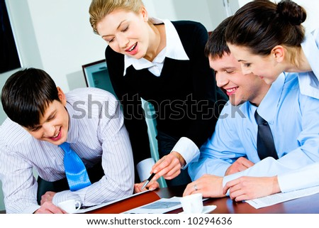 Group of four happy business partners looking at business plan lying on the table with some papers and two cups on it