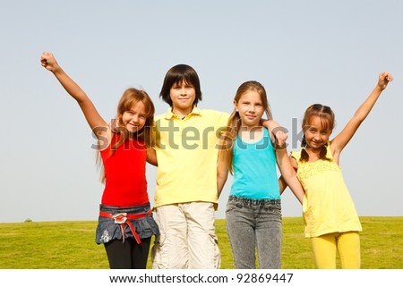 Group of four happy children jumping outdoors. - stock photo