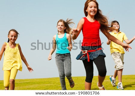 Group of four  happy children running outdoors. - stock photo