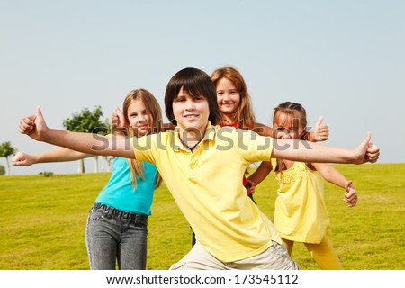 Group of four happy children show thumbs up outdoors.