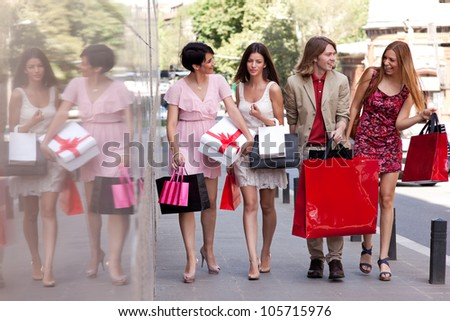 Group of four happy fashionable friends walking on the street smiling and holding colorful shopping bags.
