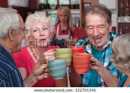 Group of four happy seniors with mugs toasting - stock photo