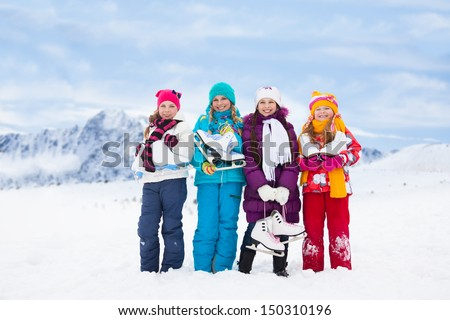 Group of four happy smiling Caucasian girls friends standing outside with ice-skates - stock photo