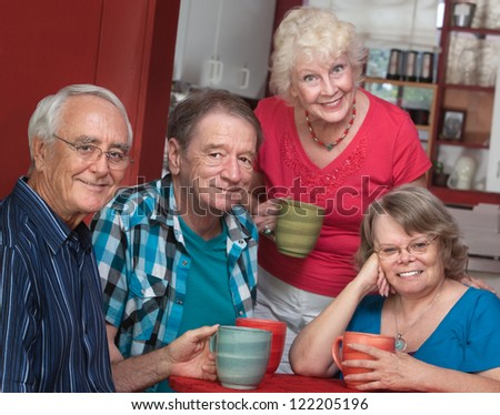 Group of four joyful senior citizens in bistro