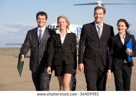 Group of four leaders smiling on the background of the airplane - stock photo