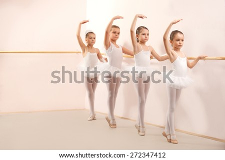 Group of four little ballerinas standing in row and practicing ballet and using stick on the wall. They are good friend and amazing dance performers - stock photo