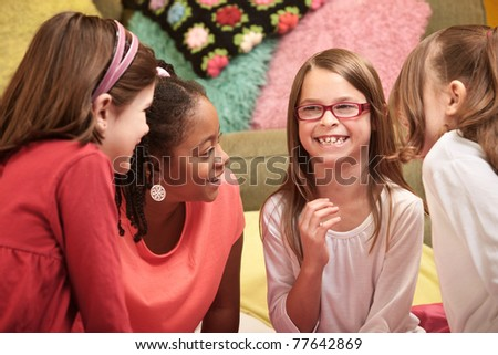 Group of four little girls laugh at a sleepover - stock photo