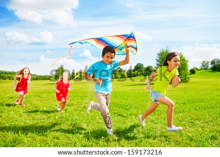Group of four little kids, boy and girls running with kite in the park on summer day - stock photo