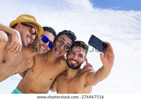 Group of four male friend taking a selfie at the beach - stock photo