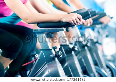 Group of four people biking in the gym, exercising their legs doing cardio training - stock photo