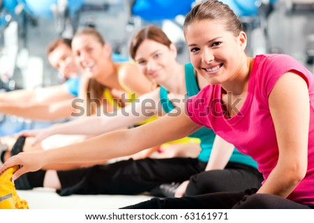 Group of four people in colorful cloths in a gym doing aerobics or warming up with gymnastics and stretching exercises - stock photo