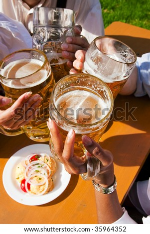 Group of four people in Couple in traditional Bavarian dress, Lederhosen and Dirndl, in a beer garden or at a festival like the Oktoberfest; focus on beer steins - stock photo