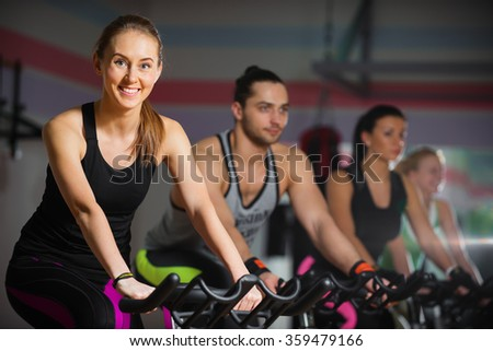 Group of four people in the gym, exercising their legs on cycles - stock photo