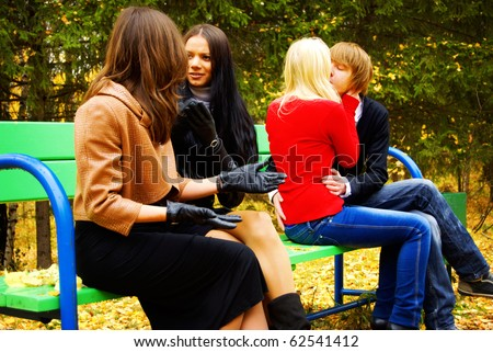 Group Of Four People Sitting On Bench In Autumn Park. Young Couple Kissing. Two Adult Women Laugh At Them. - stock photo