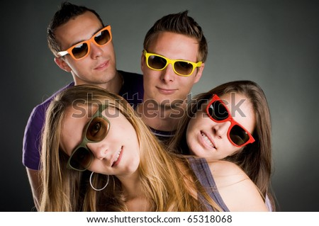 group of four persons with multi colored sunglasses - stock photo