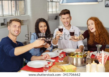 Group of Four Professional Young Friends Having a Dinner Together, Holding Glasses of Wine and Smiling at the Camera. - stock photo
