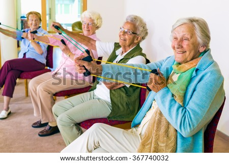 Group of four smiling senior women toning their arms with elastic strengthening bands while seated in fitness class - stock photo