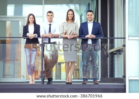 Group of four smiling young business people standing in front of the modern office building. They are leaning on the railing of the balcony and looking at camera.