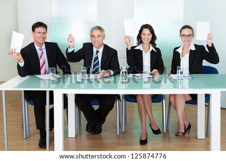 Group of four stylish professional judges seated at a long table holding up blank cards for their scores - stock photo