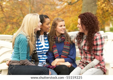 Group Of Four Teenage Girls Sitting And Chatting On Bench In Autumn Park