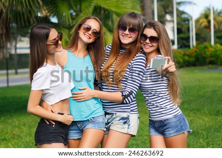 Group Of Four Teenage Girls Taking Picture In summer Park taking selfie photo using smartphone - stock photo