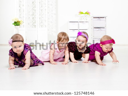 Group of four toddler girls in festive dresses crawling - stock photo