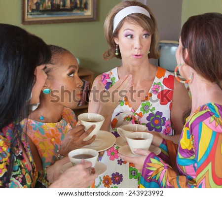Group of four women talking and drinking tea - stock photo