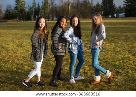 Group of four young girl firends standing and posing outside