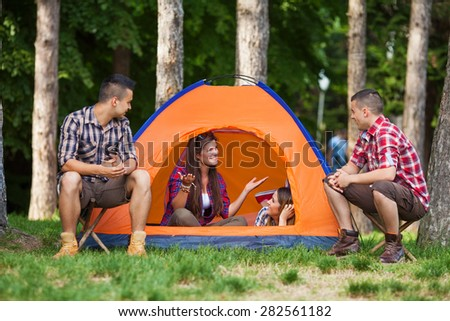 Group of four young people camping in a forest - stock photo