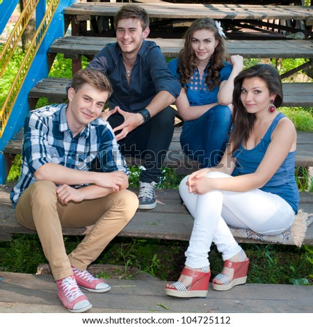 Group of four young people happy smiling having fun by posing outdoors in spring or summer on the bridge stairs