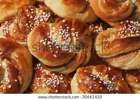 Group of fresh cinnamon buns  with pearl sugar. - stock photo