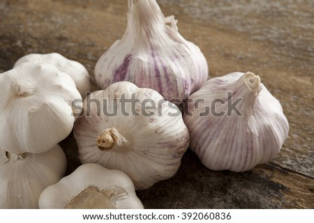 Group of fresh garlic bulbs for use as a pungent aromatic seasoning in cookery lying on a wooden table - stock photo
