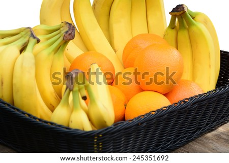 Group of fresh oranges and bananas in a green basket on a table on white - stock photo
