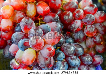 Group of fresh organically grown red grapes in the farmer market at Puyallup, Washington, USA. A close up full frame of grapes. - stock photo