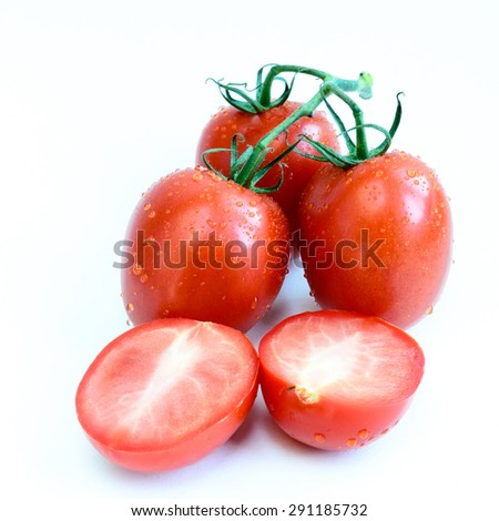 Group of fresh ripe Roma Tomatoes and slice cuts with water drops isolated on white background. Close-up view of Roma tomatoes, also known as Italian tomatoes or Italian plum tomatoes. - stock photo