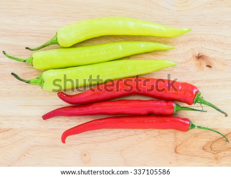 Group of freshly picked ripe chili peppers on wooden background. - stock photo