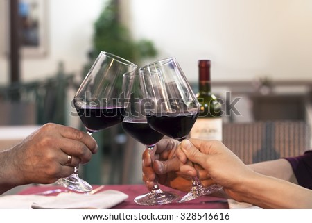 Group of friend clinking glasses of wine in a restaurant - stock photo
