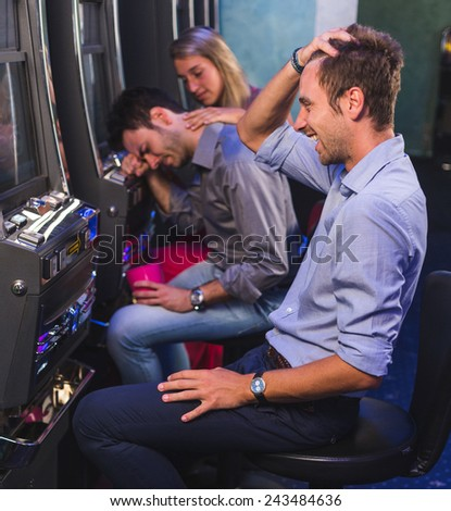 Group of Friend Playing with Slot Machines - stock photo